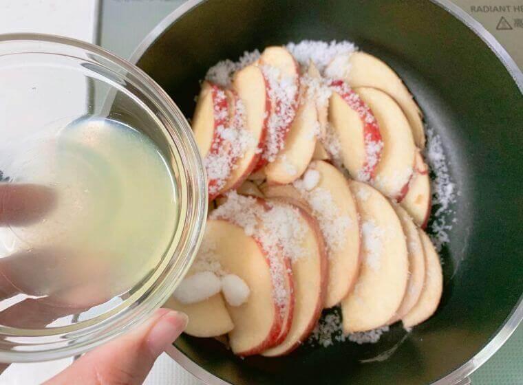 鍋にりんごを並べて砂糖とレモン汁をかけているところ