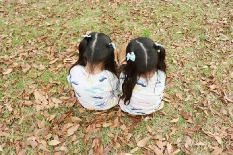 背中を向けて遊ぶ双子の女の子