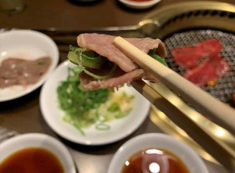 ネギ塩牛タンをお箸にとった写真