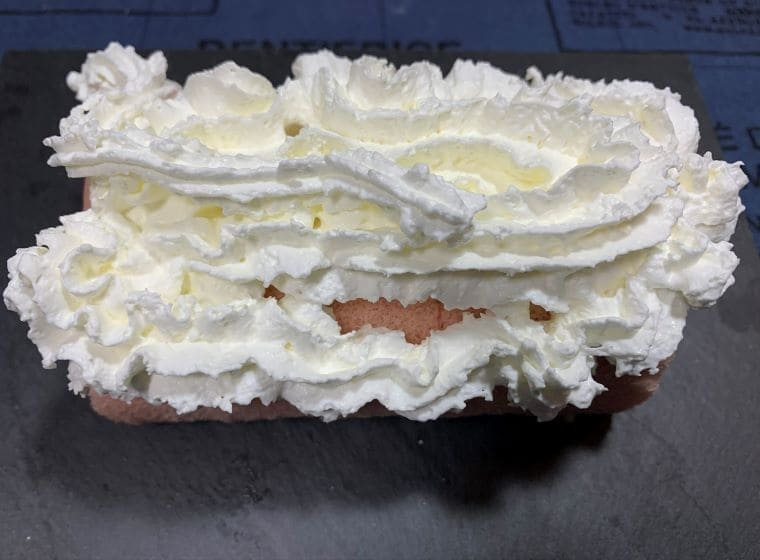 市販のロールケーキの上に業務スーパーのホイップクリームスプレーをした写真