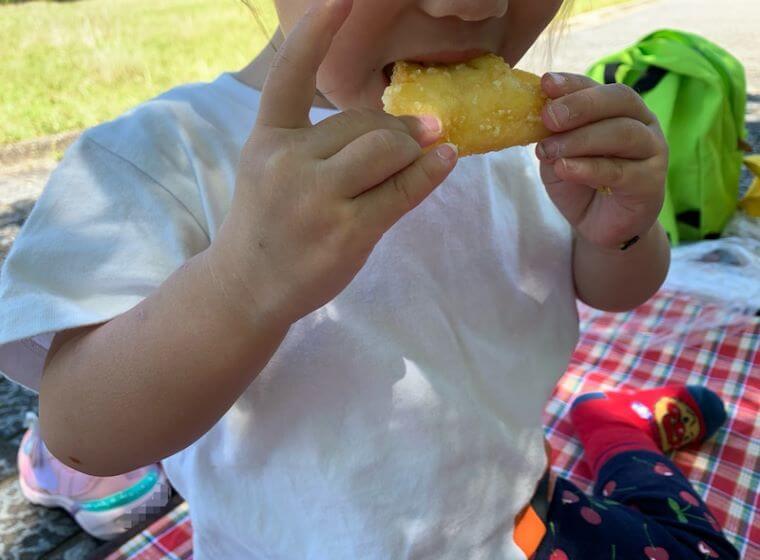 業務スーパーのチーズポテトを食べている3歳の女の子