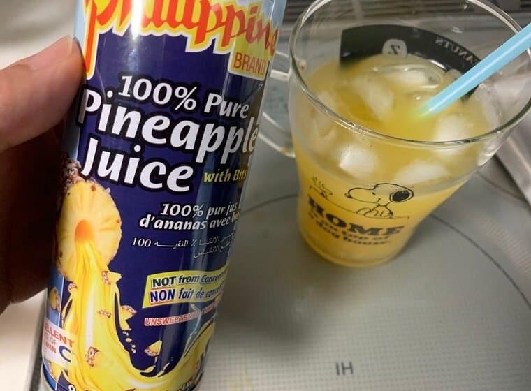 業務スーパーのパイナップルジュースをコップに注いだ写真